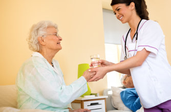nurse brings water to immobile senior woman at nursing home